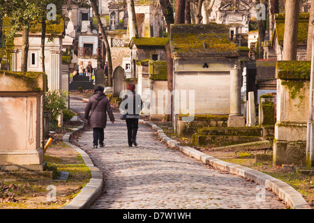 People walking past the gravestones of Pere Lachaise cemetery, Paris, France - Stock Photo