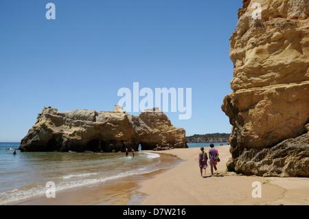 People walking and paddling near sandstone cliffs and rocks at Praia da Rocha beach, Portimao, Algarve, Portugal - Stock Photo