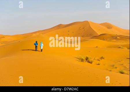 Two Berber men walking in the sand dunes of Erg Chebbi Desert, Sahara Desert near Merzouga, Morocco, North Africa - Stock Photo
