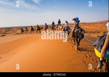Tourists on a camel ride in Erg Chebbi Desert, Sahara Desert near Merzouga, Morocco, North Africa - Stock Photo