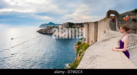 Tourist on Dubrovnik City Walls, with Fort Lovrijenac in the background, Dubrovnik, Dalmatian Coast, Adriatic, Croatia - Stock Photo