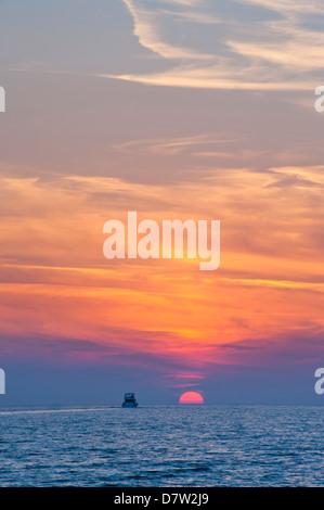 Boat driving into the sunset at Zlatni Rat Beach, Bol, Brac Island, Dalmatian Coast, Adriatic, Croatia - Stock Photo