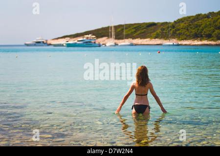 Tourist swimming on a beach in the Pakleni Islands (Paklinski Islands), near Hvar Island, Dalmatian Coast, Adriatic - Stock Photo