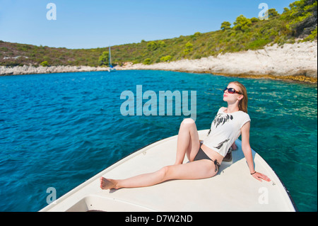 Tourist sunbathing on a boat in the Pakleni Islands (Paklinski Islands), Hvar Island, Dalmatian Coast, Adriatic - Stock Photo