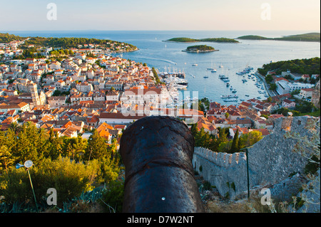 Hvar Fortress cannon and Hvar Town at sunset taken from the Spanish Fort, Hvar Island, Dalmatian Coast, Adriatic, - Stock Photo