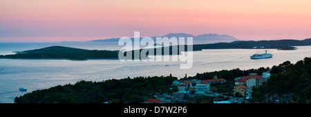 Pakleni Islands and Vis Island, a cruise ship moored at sunset, seen from Hvar Island, Dalmatian Coast, Adriatic - Stock Photo