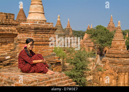 Young Burmese woman in a red dress sitting on the roof of a temple, Bagan (Pagan), Burma - Stock Photo