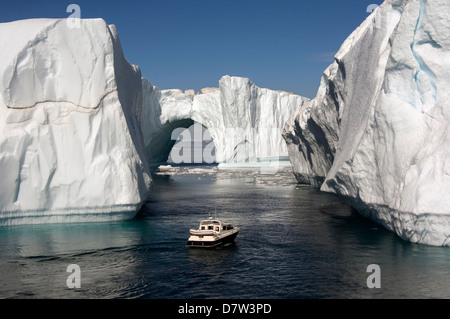 Icebergs in Disko Bay, natural arch and motorboat, UNESCO World Heritage Site, Ilulissat (Jakobshavn), Greenland, - Stock Photo