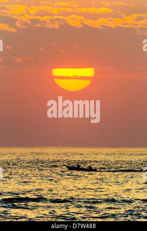 Fishing boat and sunset off Playa Guiones surf beach, Nosara, Nicoya Peninsula, Guanacaste Province, Costa Rica - Stock Photo