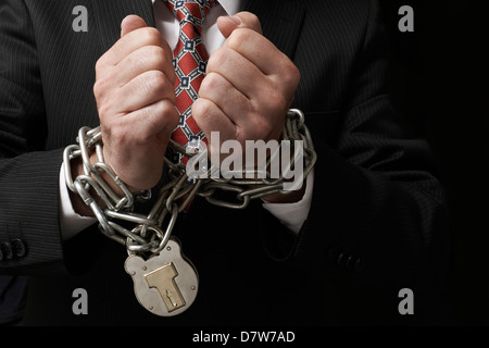 Close up of businessmans hands tied in heavy chains with padlock - Stock Photo