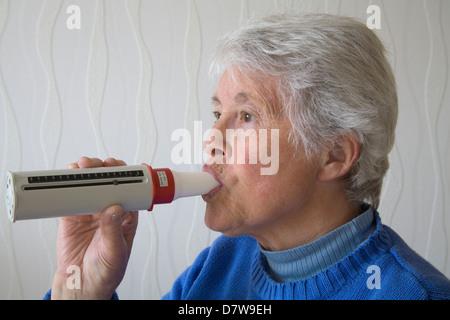UK Elderly woman blowing into peak flow meter to monitor lung capacity - Stock Photo