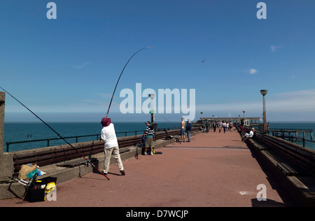 Fisherman casting off on Deal Pier,  Deal, Kent. - Stock Photo
