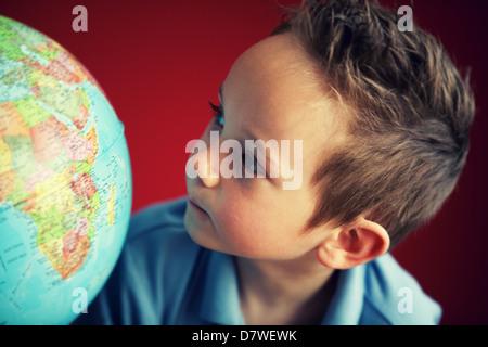 school boy looking at globe - Stock Photo