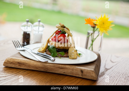Sirloin steak meal served with artichoke, Onion rings and fresh vine tomatoes on a white plate with cutlery & condiments - Stock Photo