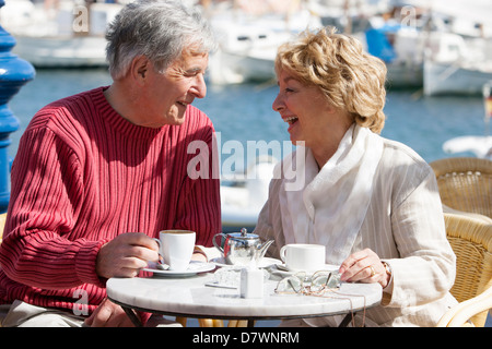 Elderly couple having a coffee in a seafront cafe - Stock Photo