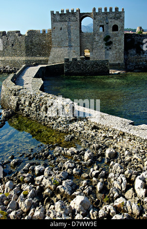 Entrance to Methoni Castle from sea at sunny summer day, rocks in foreground. - Stock Photo