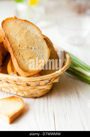 Toasted bread in the bread basket on white boards, food - Stock Photo