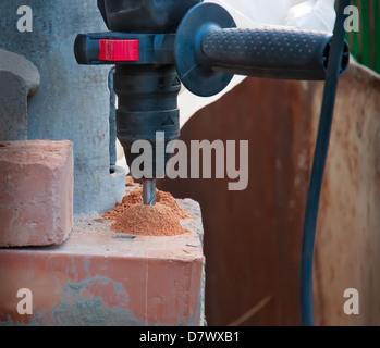 Hammer drill in a brick - Stock Photo