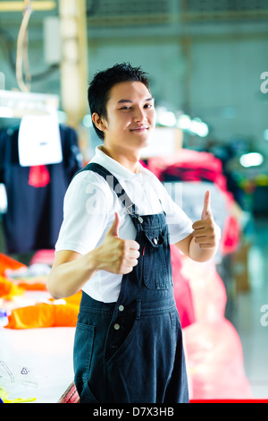 Worker or production manager standing proudly in a Chinese textile factory, it is his workplace - Stock Photo