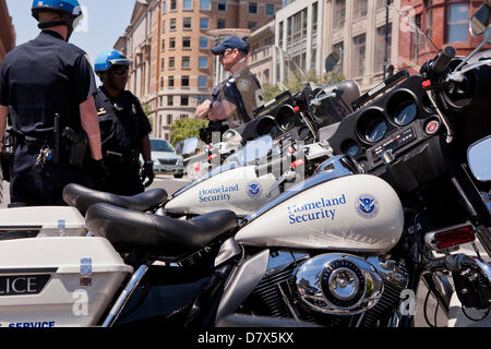 US Department of Homeland Security Federal Protective Service Police officers standing next to service motorcycle - Stock Photo