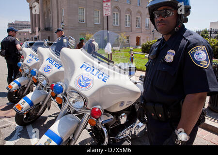US Department of Homeland Security Federal Protective Service Police officer standing next to service motorcycle - Stock Photo