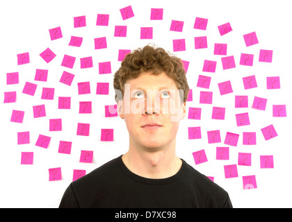 Young man with pink sticky notes and question marks thinking about decision making - Stock Photo
