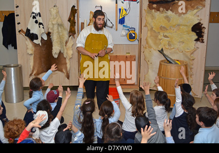 Young children get a lesson in how Torahs are made at the Jewish Children's Museum in Crown Heights, Brooklyn, New - Stock Photo