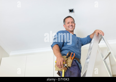 Man working on ceiling lights - Stock Photo