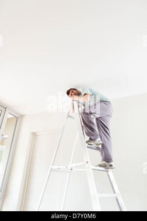 Man climbing ladder indoors - Stock Photo
