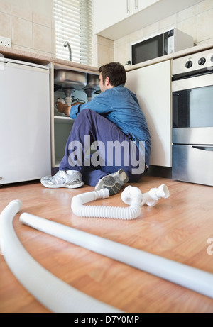 Plumber working on pipes under sink - Stock Photo