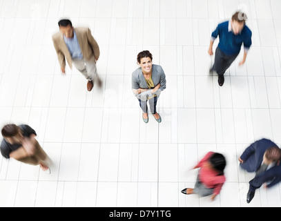 Businesswoman standing in busy office hallway - Stock Photo