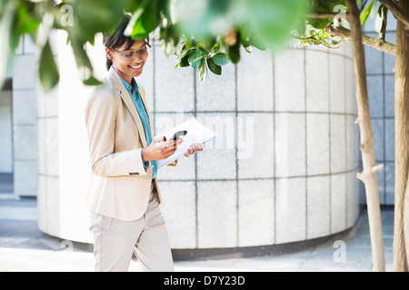Businesswoman using cell phone outdoors - Stock Photo