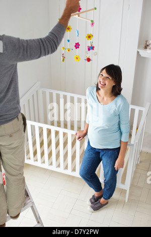 Couple decorating new baby's room - Stock Photo