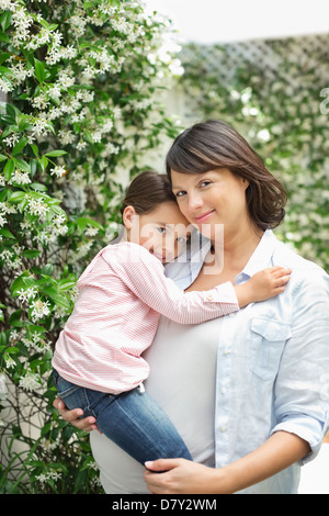 Pregnant mother holding daughter outdoors - Stock Photo