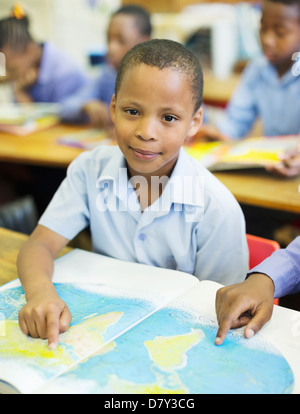 Students using world map in class - Stock Photo