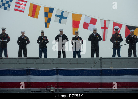 Sailors and Marines man the rails of USS Anchorage. - Stock Photo