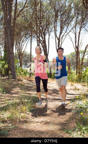 Couple running on dirt path - Stock Photo