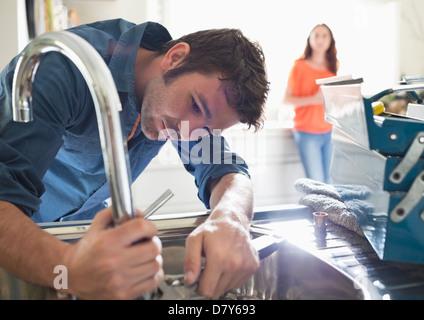 Plumber working on kitchen sink - Stock Photo