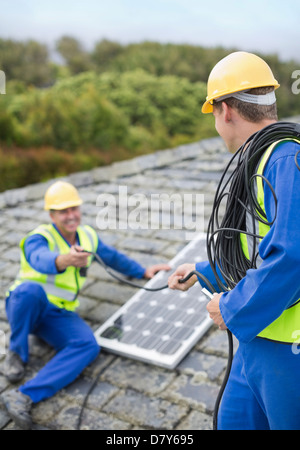 Workers Installing Solar Panel On Roof Stock Photo