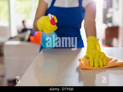 Woman cleaning kitchen counter - Stock Photo