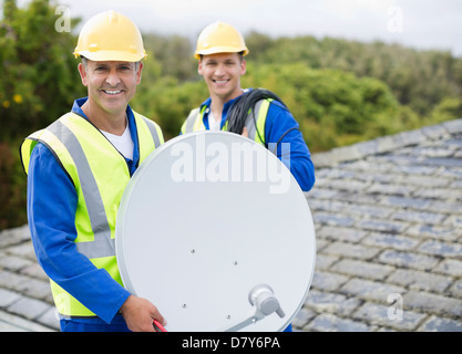 Workers installing satellite dish on roof - Stock Photo