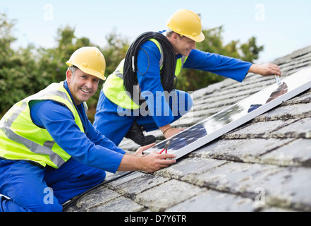 Workers installing solar panels on roof - Stock Photo