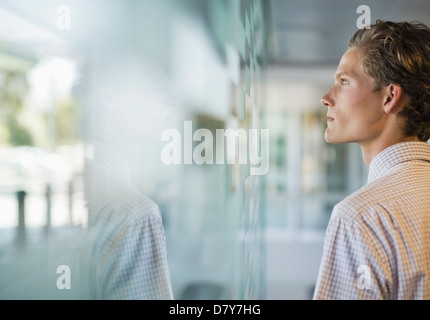 Businessman looking out office window - Stock Photo