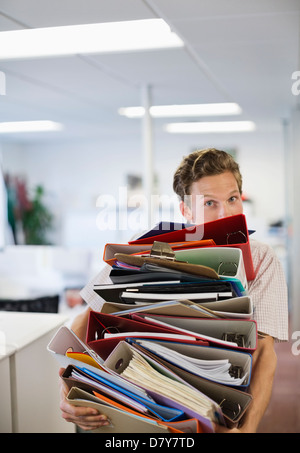 Businessman balancing folders in office - Stock Photo