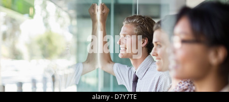 Business people looking out office window - Stock Photo