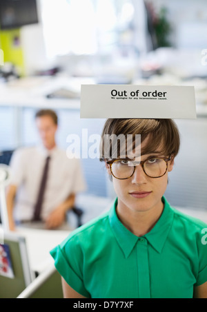 Businesswoman wearing 'out of order' sign