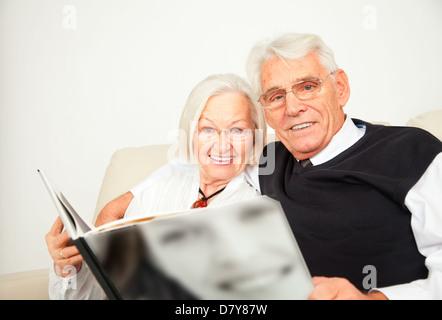 Senioren Paar sitzt auf dem Sofa und schauen ein Buch an - Stock Photo