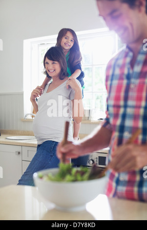 Pregnant mother and daughter watching father toss salad - Stock Photo