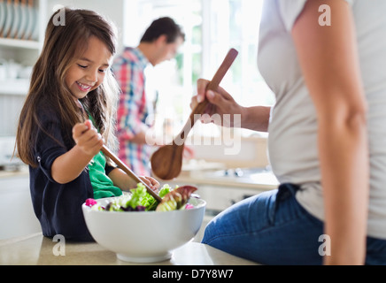 Mother and daughter tossing salad together - Stock Photo