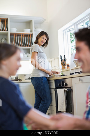 Pregnant mother cooking in kitchen - Stock Photo